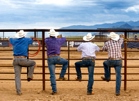 Four cowboys with their backs to the camera, each with a leg up on the fence.