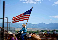A young cowboy holding the flag before the start of the ranch rodeo